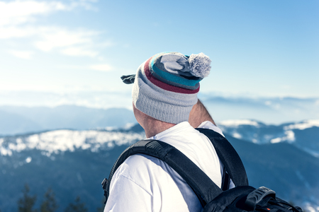Middle aged man looking far away from the top of the mountain. Warmer highlights, shallow depth of field. photo