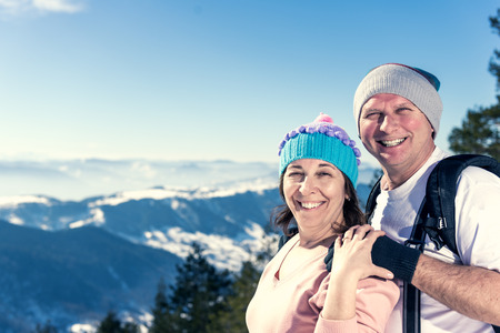 Smiling middle aged couple smiling and looking at the camera on the top of the mountain. Warmer tones in the highlights because of the Sun. Copy space on the left side of the frame, shallow depth of field. Real People Stock Photo
