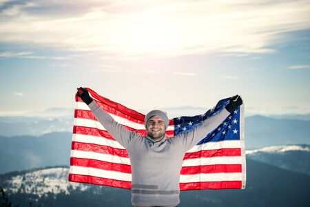 Young man holding USA flag on the top of the mountain with raised hands. Warm tones in highlights lens flare copy space