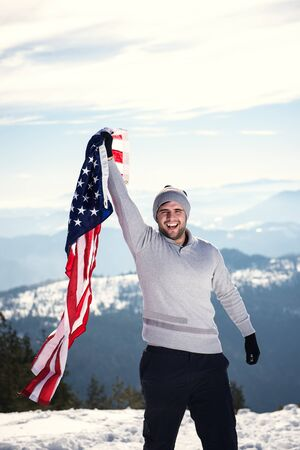 overexposed: Young cheerful happy man holding USA flag on the top of the mounain with one hand. Copy space on the top overexposed highlights Stock Photo