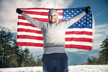 spreaded: Young cheerful happy man with a big smile holding USA flag on the top of the mounain with spreaded hands. Stock Photo