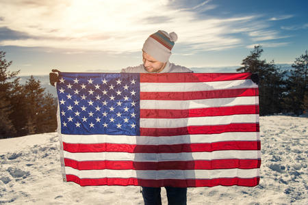 spreaded: Winter scene, young man holding USA flag with spreaded hands. Copy space Stock Photo