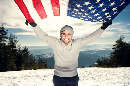 warmer: Cheerful happy young man with a big smile holding USA flag looking at the camera and smiling. Warmer highlights lens flare