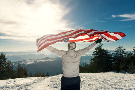 warmer: Young man holding USA flag with spreaded hands looking away. Shallow depth of field warmer highlights lens flare