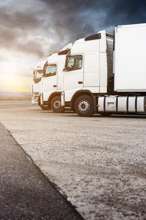 Drie witte vrachtwagens op een rij te wachten voor de volgende bestelling. Dramatische hemel, voegde lens flare en warme tinten. Kopieer ruimte aan de onderkant van het frame.