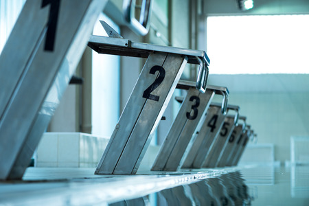 swimming pool float: Starting blocks in row by the swimming pool, selective focus, toned image Stock Photo