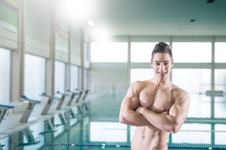 naked youth: Young muscular swimmer standing by the pool and looking at the camera, selective focus, toned image