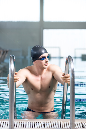 exiting: Professional swimmer after the race, using ladder, exiting the pool. Looking away from the camera, copy space on the top of the frame