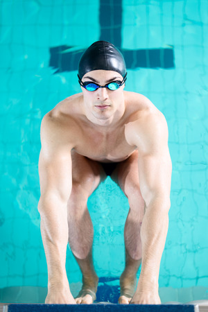 swimming race: Professional swimmer preparing for a swimming race and diving off the starting block. Copy space