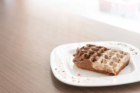 narrow depth of field: Belgian waffle with eurocream on the wooden table. Selective focus, narrow depth of field