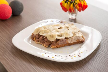 narrow depth of field: Belgian waffle with sweet creme and banana on the top. Selective focus, narrow depth of field Stock Photo