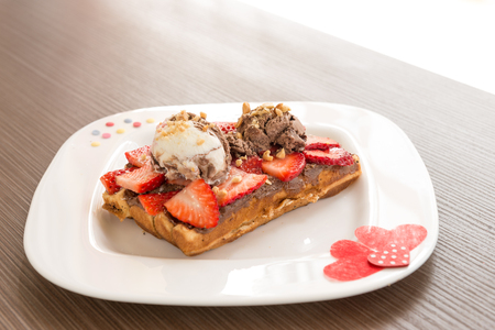 narrow depth of field: Belgian waffle with ice cream and strawberry. Selective focus, narrow depth of field