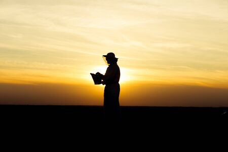 apiarist: Apiarist silhouette in the field holding a smoker at sunset. Warm tones, sunlight Stock Photo