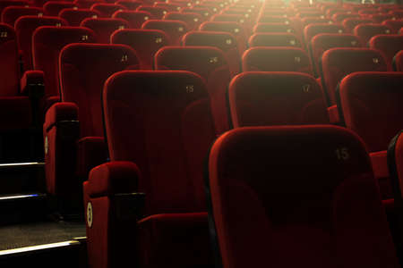 light play: Red empty numbered theateramphitheatre  seats with yellow backlight. Stock Photo