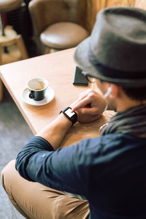 angle bar: Young stylish and fashionable man checking his smartwatch in cafe bar. High angle shot. Selective focus. Toned image. Stock Photo