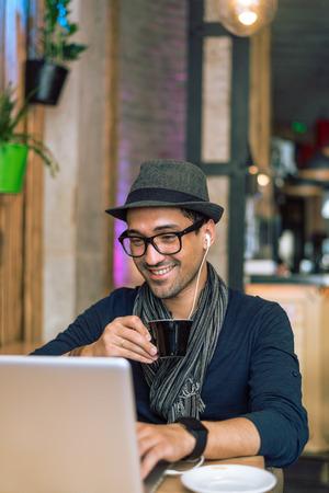 jovenes estudiantes: Hombre joven de moda y con estilo que se relaja con caf�, la m�sica y la navegaci�n por Internet en el bar cafeter�a. Enfoque selectivo. Imagen entonada
