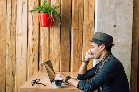 lifestyle: Trendy en stijlvolle jonge man praten aan de telefoon, ontspannen met koffie, muziek en surfen op het internet in het café bar. Selectieve aandacht. Profiel shot. Getinte afbeelding