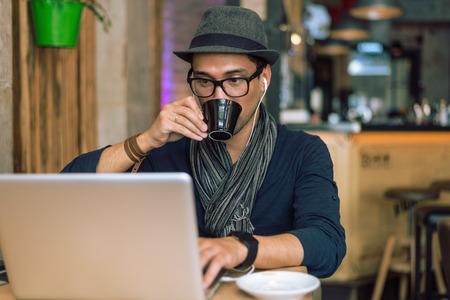 hombre tomando cafe: Joven caf� de moda y con estilo beber, escuchar m�sica y navegar por internet en el bar cafeter�a. Enfoque selectivo. Enton� la imagen.