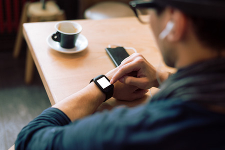 Young stylish and fashionable man checking his smartwatch in cafe bar. High angle shot. Selective focus. Toned image. Stockfoto
