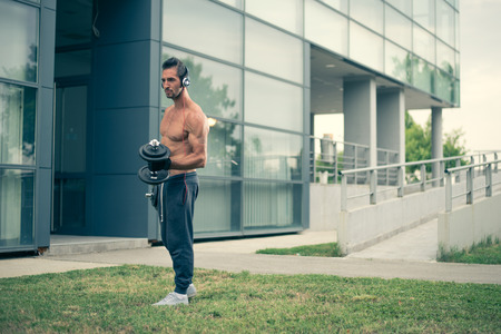 male body: Young man listening to the music and working out with dumbbells in front of the modern sport centar. Wearing tracksuits without shirt. Selective focus Stock Photo