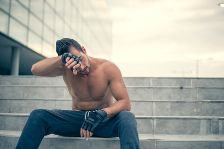 Young man relaxing and wiping sweat from his face after very heavy workout. Selective focus.