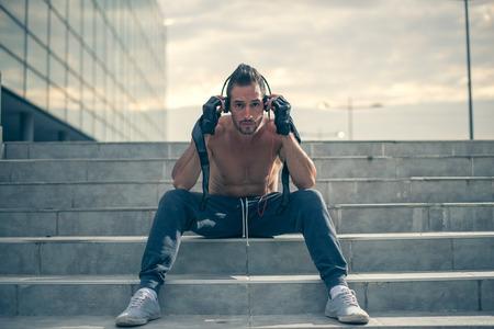 muskeltraining: Erste Schritte zum harten Training motiviert, h�ren die Musik mit Kopfh�rer auf und Handschuhe f�r trainning. Selektiver Fokus Lizenzfreie Bilder