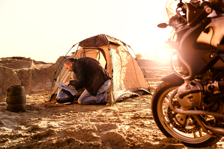 motorbike: Middle aged motorcyclist relaxing after a long ride on motorbike. Checking his travel map in tent. Lens flare. Warm colors. Selective focus.
