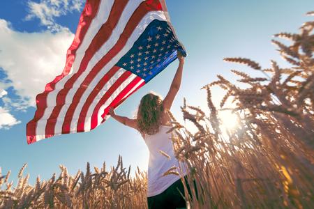 젊은 행복 소녀 실행 및 밀 필드 위에 팔을 벌려 평온한 점프. 미국 국기를 들고. 톤 이미지입니다. 선택적 중점을두고 있습니다.