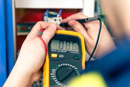 ingenieria elÉctrica: electricista varón joven que toma el cuidado de la seguridad.