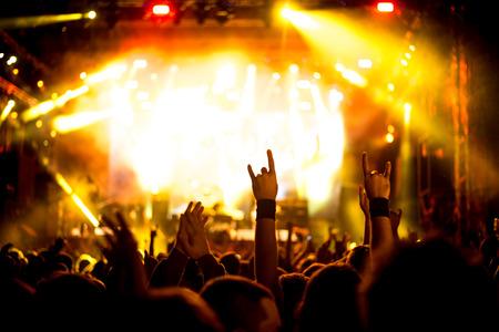 imagen: Una multitud de personas celebran y de fiesta con sus manos en el aire a una impresionante Dj. Alta imagen granulada ISO.