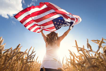 american flags: Young happy girl running and jumping carefree with open arms over wheat field. Holding USA flag. Toned image. Selective focus.