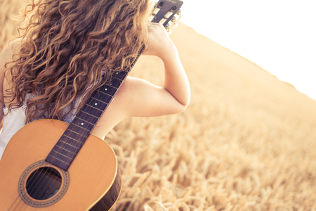 Beautiful young girl carryng her guitar through the golden wheat field. Lens flare, selective focus, toned image. Stock Photo