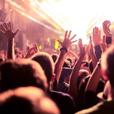 A crowd of people celebrating and partying with their hands in the air to an awesome Dj. High ISO grainy image. Stockfoto