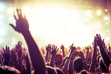 party dj: Una multitud de personas celebran y de fiesta con sus manos en el aire a una impresionante Dj. Alta imagen granulada ISO.