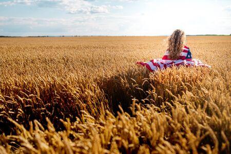 bandera blanca: Muchacha feliz joven correr y saltar sin preocupaciones con los brazos abiertos sobre campo de trigo. La celebraci�n de EE.UU. bandera. Entonado imagen. Enfoque selectivo. Foto de archivo