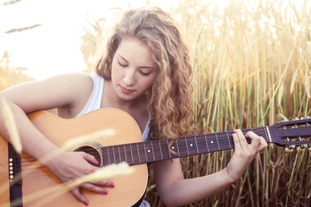 Beautiful young girl playing guitar in the golden wheat field. Lens flare, selective focus, toned image.