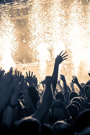 show hands: Una multitud de personas celebran y de fiesta con sus manos en el aire a una impresionante Dj. Alta imagen granulada ISO.