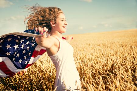 Jong gelukkig meisje uitgevoerd en springen zorgeloos met open armen over tarweveld. Het houden van USA vlag. Gestemd beeld. Selectieve aandacht. Stockfoto