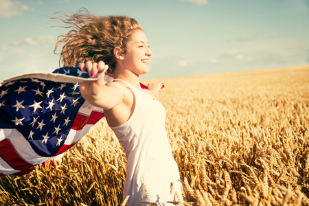 usa patriotic: Young happy girl running and jumping carefree with open arms over wheat field. Holding USA flag. Toned image. Selective focus.