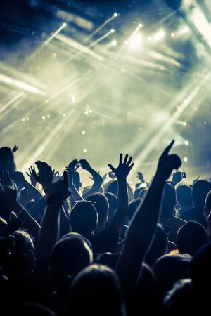 축하와 멋진 디제이로 공중에 자신의 손으로 파티 사람들의 군중. 고 ISO 거친 이미지입니다. 소프트 포커스.