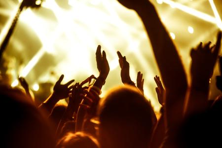 concierto de rock: Una multitud de personas celebran y de fiesta con sus manos en el aire a una impresionante Dj. Alta imagen granulada ISO. Enfoque suave. Foto de archivo