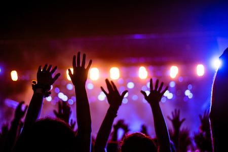 음악 축제에서 제기 된 손과 무대 위에서 스트리밍되는 조명. 소프트 포커스, 흐리게 운동입니다. 스톡 콘텐츠