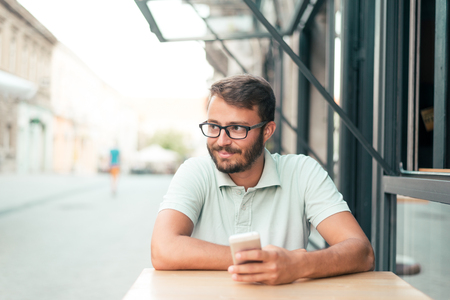 fun at work: Shot of a young businessman on the phone while sitting in a coffee shop. Stock Photo