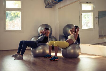 gym clothes: Young couple working on the exercise balls at the gym. Stock Photo