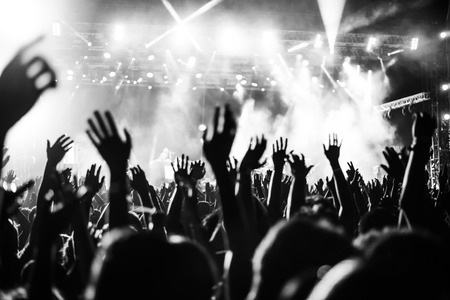 Black and white photo of audience with hands raised at a music festival and lights streaming down from above the stage. Soft focus, blurred movement. Stockfoto