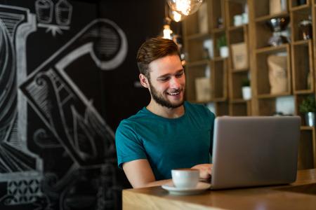 그의 노트북 카페에서가 게에서 작동하는 젊은 사업가의 총. 선택적 포커스입니다.