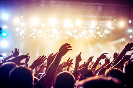 festivals: Audience with hands raised at a music festival and lights streaming down from above the stage. Soft focus, blurred movement. Stock Photo