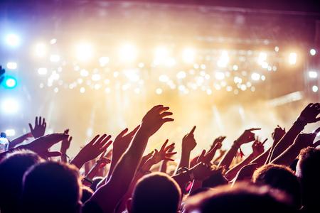 alzando la mano: Audiencia con las manos levantadas en un festival de música y luces de streaming desde arriba del escenario. Enfoque suave, el movimiento borroso. Foto de archivo