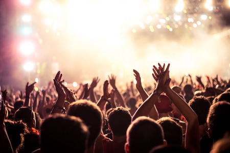 dancing club: Audience with hands raised at a music festival and lights streaming down from above the stage. Soft focus, blurred movement. Stock Photo