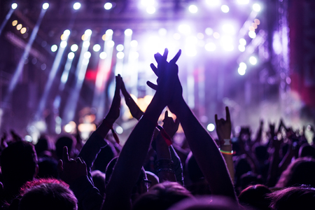 Audience with hands raised at a music festival and lights streaming down from above the stage. Soft focus, blurred movement. Stockfoto